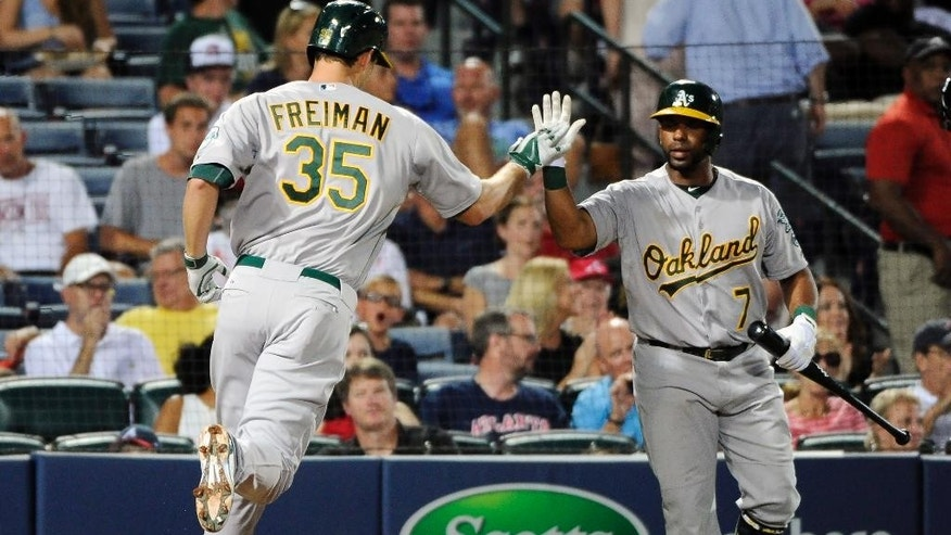 Oakland Athletics' Nate Freiman (35) is congratulated by teammate Alberto Callaspo (7) after Frieman's two-run home run against the Atlanta Braves during the fourth inning of a baseball game Friday, Aug. 15, 2014, in Atlanta. (AP Photo/David Tulis)