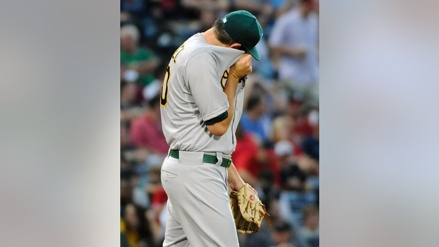 Oakland Athletics starting pitcher Jason Hammel wipes his face after giving up the second of two back-to-back home runs to the Atlanta Braves during the second inning of a baseball game Friday, Aug. 15, 2014, in Atlanta. (AP Photo/David Tulis)