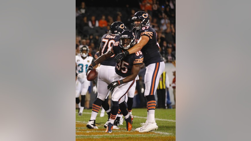 Chicago Bears running back Senorise Perry (35) celebrates after scoring the game-winning touchdown with teammate Jeron Mastrud (87) during the second half of an NFL preseason football game against the Jacksonville Jaguars in Chicago, Thursday, Aug. 14, 2014. The Bears won 20-19. (AP Photo/Andrew Nelles)