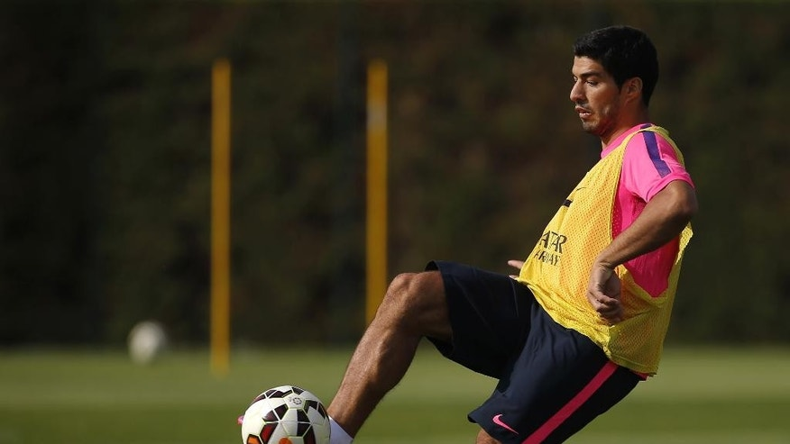Luis Suarez, of Uruguay, controls a ball during a training session at the Sports Center FC Barcelona Joan Gamper in San Joan Despi, in Barcelona, Spain, Friday, Aug. 15, 2014. Suarez trained with his Barcelona teammates on Friday after his ban for biting an opponent at the World Cup was softened but not shortened. The Court of Arbitration for Sport ruled Thursday that the Uruguay forward, who recently left Liverpool for Barcelona, deserves his four-month ban from playing official matches for both his club and his country. (AP Photo/Emilio Morenatti )
