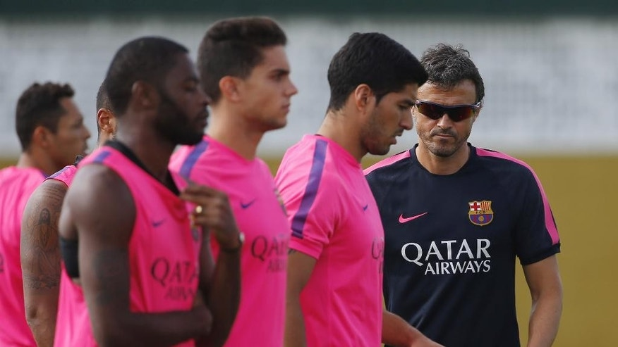Barcelona head coach Luis Enrique, right, walks next to Luis Suarez, center, from Uruguay, during a training session at the Sports Center FC Barcelona Joan Gamper in San Joan Despi, in Barcelona, Spain, Friday, Aug. 15, 2014. Suarez trained with his Barcelona teammates on Friday after his ban for biting an opponent at the World Cup was softened but not shortened.The Court of Arbitration for Sport ruled Thursday that the Uruguay forward, who recently left Liverpool for Barcelona, deserves his four-month ban from playing official matches for both his club and his country. (AP Photo/Emilio Morenatti )
