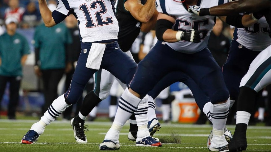 New England Patriots quarterback Tom Brady (12) passes against the Philadelphia Eagles behind a block by tackle Jordan Devey (65) in the first quarter of an NFL football game Friday, Aug. 15, 2014, in Foxborough, Mass. (AP Photo/Elise Amendola)