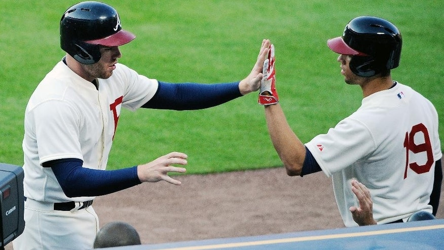Atlanta Braves' Freddie Freeman, left, is congratulated by Andrelton Simmons (19) after scoring against the Oakland Athletics on a Chris Johnson single during the first inning of a baseball game Saturday, Aug. 16, 2014, in Atlanta. (AP Photo/David Tulis)