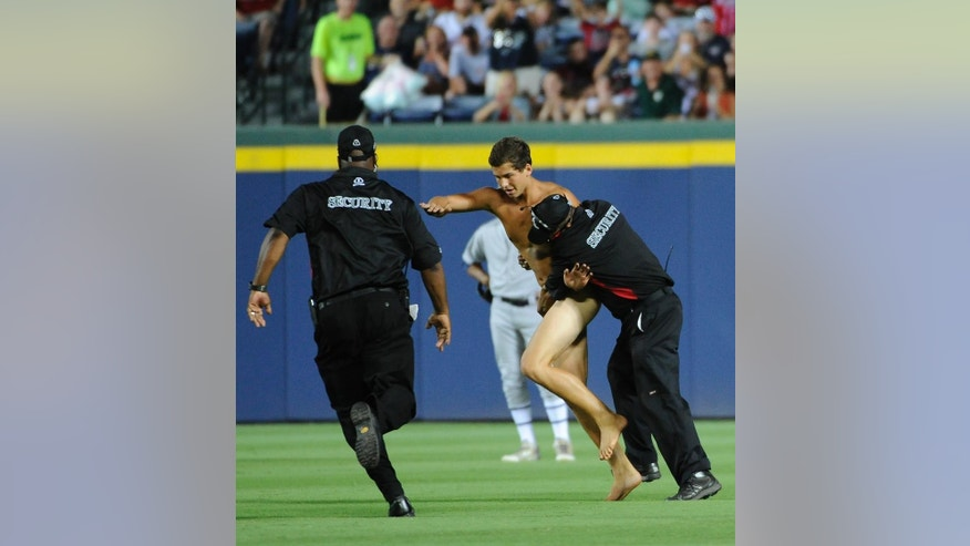Time is halted as a streaker is confronted by Atlanta Braves security personnel during the sixth inning of a baseball game against the Oakland Athletics Saturday, Aug. 16, 2014, in Atlanta. (AP Photo/David Tulis)