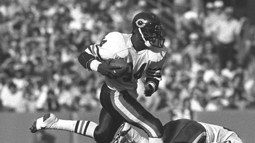 FILE - In this Nov. 11, 1984, file photo, Chicago Bears running back Walter Payton leaps over Los Angeles Rams linebacker Jim Collins (50) during first half football action in Anaheim, Calif. Long before quarterbacks took center stage, the NFL was a running backs league. From Red Grange to Jim Brown to O.J. Simpson to Walter Payton to Emmitt Smith, the workhorse back has been a symbol of toughness and perseverance. (AP Photo/Reed Saxon, File)