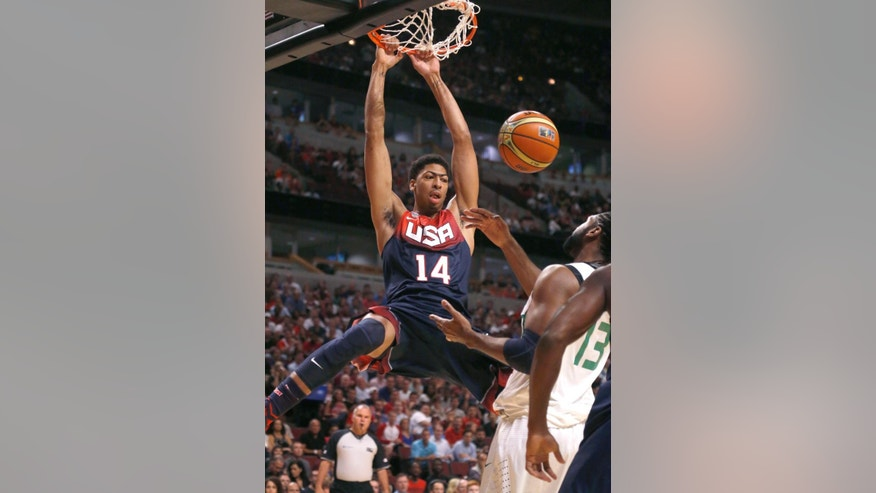 United States' Anthony Davis (14), of the New Orleans Pelicans, dunks over Brazil's Nene Hilario, of the Washington Wizards, during the first half of an exhibition basketball game Saturday, Aug. 16, 2014, in Chicago. (AP Photo/Charles Rex Arbogast)