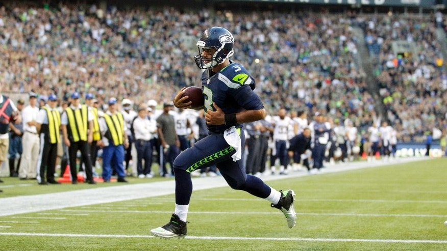 Seattle Seahawks quarterback Russell Wilson rushes for a touchdown against the San Diego Chargers in the first half of a preseason NFL football game, Friday, Aug. 15, 2014, in Seattle. (AP Photo/Stephen Brashear)