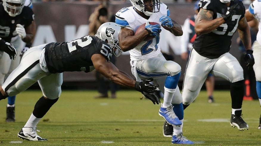 Detroit Lions running back Reggie Bush (21) runs between Oakland Raiders outside linebacker Khalil Mack, left, and defensive end LaMarr Woodley (57) during the first half of an NFL preseason football game in Oakland, Calif., Friday, Aug. 15, 2014. (AP Photo/Marcio Jose Sanchez)