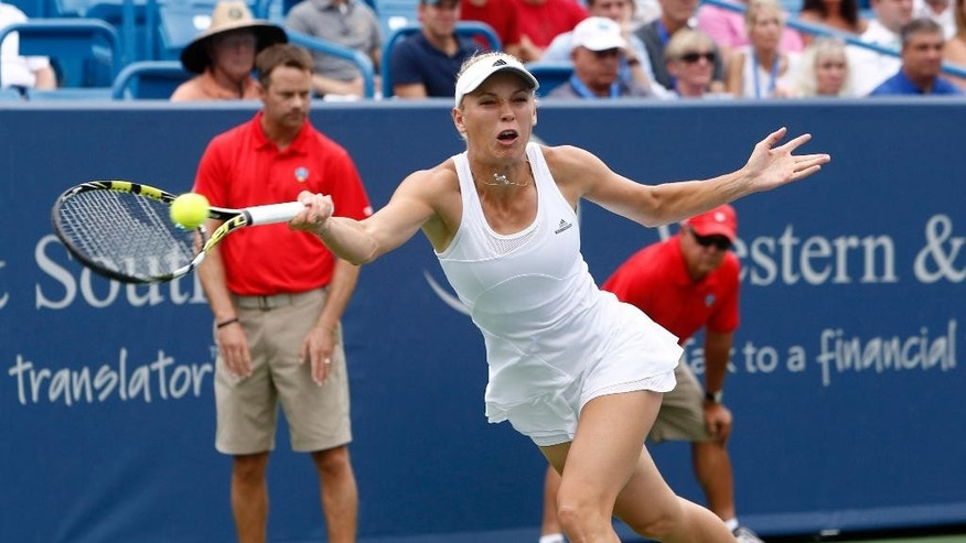Caroline Wozniacki, from Denmark, returns to Serena Williams during a semifinal match at the Western & Southern Open tennis tournament, Saturday, Aug. 16, 2014, in Mason, Ohio. (AP Photo/David Kohl)