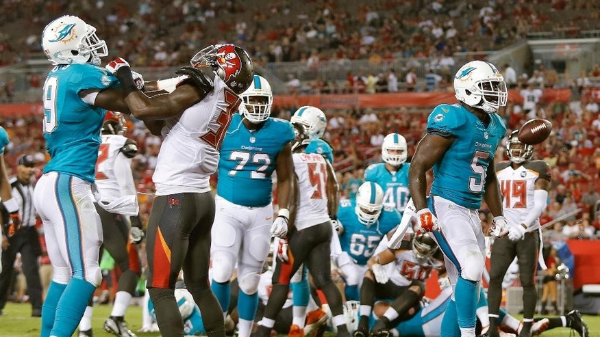 Miami Dolphins running back Damien Williams (5) spikes the football after scoring on a 1-yard touchdown run against theTampa Bay Buccaneers during the third quarter of an NFL preseason football game Saturday, Aug. 16, 2014, in Tampa, Fla. (AP Photo/Brian Blanco)