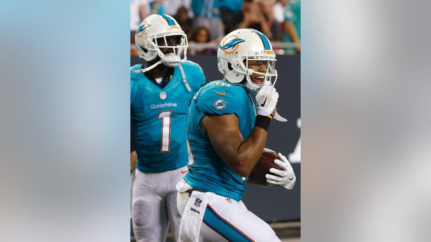 Miami Dolphins wide receiver Rishard Matthews (18) celebrates with wide receiver Damian Williams after scoring against the Tampa Bay Buccaneers during the second quarter of an NFL preseason football game Saturday, Aug. 16, 2014, in Tampa, Fla. (AP Photo/Brian Blanco)