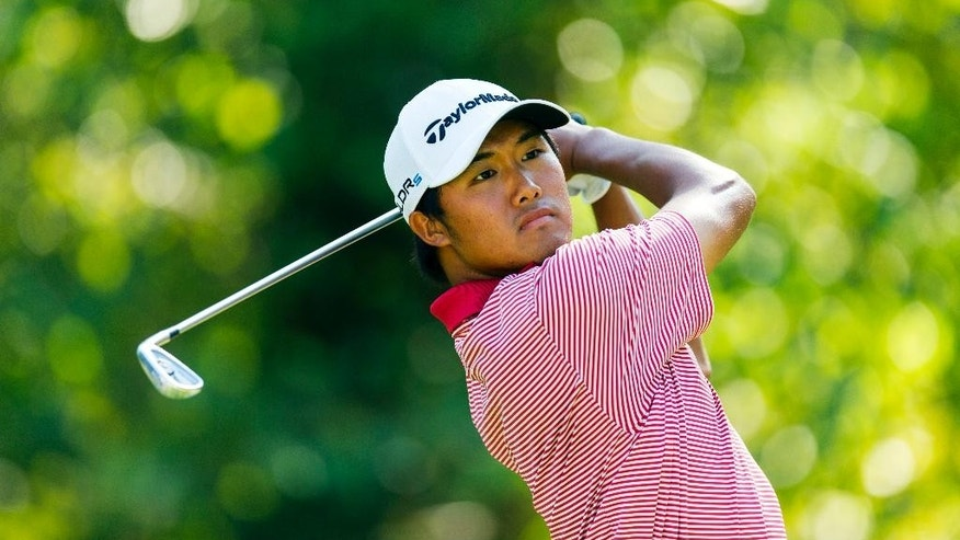 In this photo released by the USGA, Gunn Yang, of South Korea, watches his tee shot on the 13th hole during the semifinal round of match play at the U.S. Amateur Championship golf tournament at Atlanta Athletic Club in Johns Creek, Ga., Saturday, Aug. 16, 2014.  (AP Photo/USGA, Chris Keane)