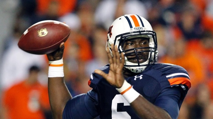 FILE - In this Oct. 26, 2013, file photo, Auburn quarterback Jeremy Johnson rolls out to pass during the first half of an NCAA college football game against Florida Atlantic in Auburn, Ala.  Johnson says he has no idea if he's starting against Arkansas with starter Nick Marshall being held out for at least the opening. He does have one prediction: Marshall will win the Heisman Trophy. (AP Photo/Butch Dill, File)