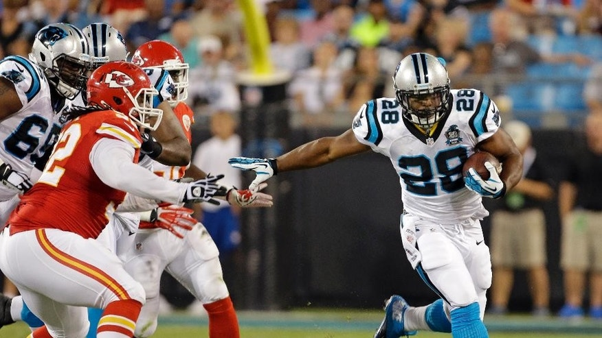 Carolina Panthers' Jonathan Stewart (28) runs past Kansas City Chiefs' Dontari Poe (92) during the first half of an NFL preseason football game in Charlotte, N.C., Sunday, Aug. 17, 2014. (AP Photo/Bob Leverone)