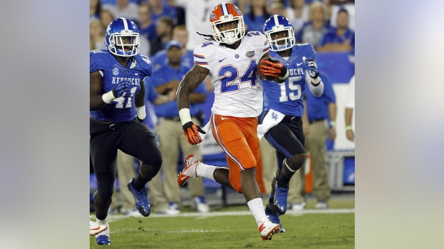 FILE - In this Sept. 28, 2013, file photo, Florida running back Matt Jones (24) outruns Kentucky's TraVaughn Paschal, left, and Marcus McWilson (15) in the second quarter of an NCAA college football game in Lexington, Ky.  Jones was mostly miserable last season. He missed most of camp with a viral infection, rushed back and then blew out his knee early in the season. He's healthy now and eager to prove last year was a fluke. (AP Photo/James Crisp, File)