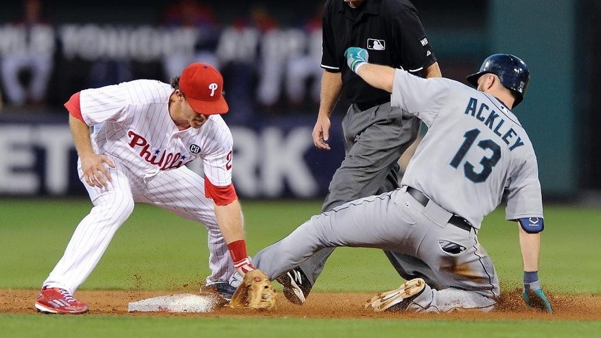 Seattle Mariners' Dustin Ackley (13) hits a double to left field and slides ahead of a tag from Philadelphia Phillies second baseman Chase Utley in the third inning of an interleague baseball game on Monday, Aug. 18, 2014, in Philadelphia. (AP Photo/Michael Perez)