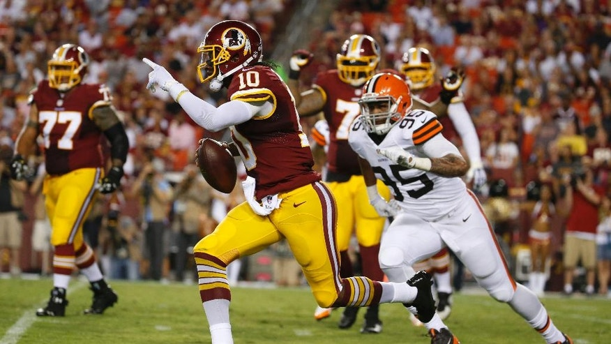 Washington Redskins quarterback Robert Griffin III (10) runs away from Cleveland Browns defensive end Armonty Bryant (95) during the first half of an NFL preseason football game Monday, Aug. 18, 2014, in Landover, Md. (AP Photo/Evan Vucci)