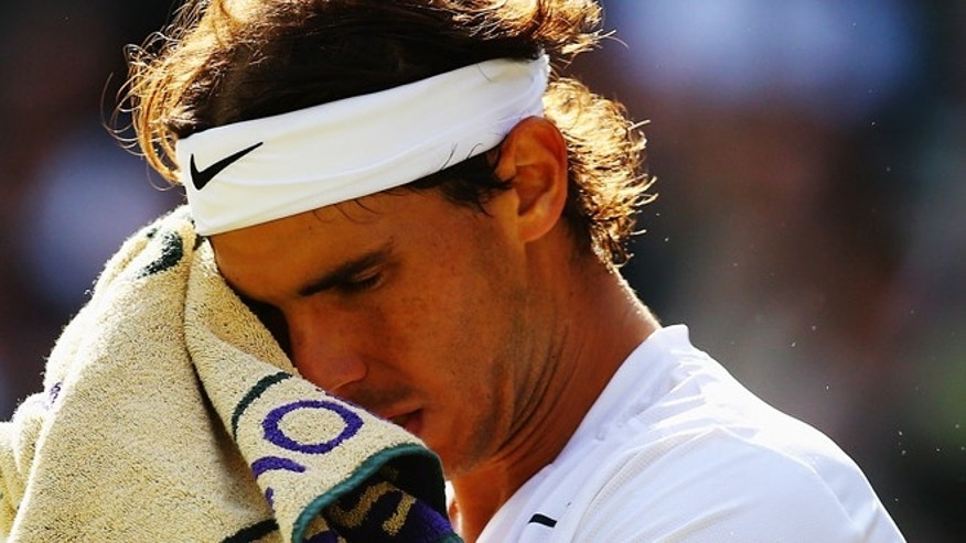 LONDON, ENGLAND - JULY 01:  Rafael Nadal of Spain stands dejected during his Gentlemen's Singles fourth round match against Nick Kyrgios of Australia on day eight of the Wimbledon Lawn Tennis Championships at the All England Lawn Tennis and Croquet Club on July 1, 2014 in London, England.  (Photo by Al Bello/Getty Images)