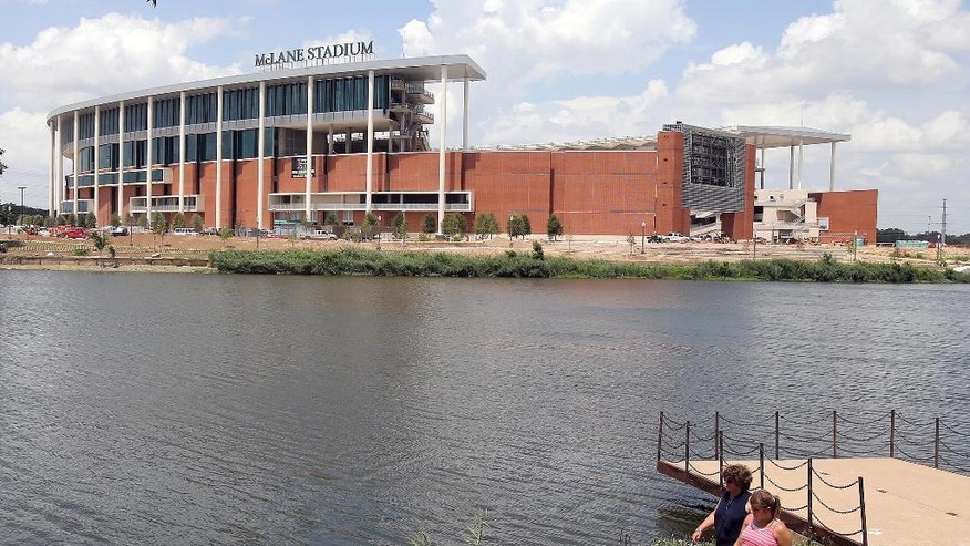 FILE - In this July 2, 2014, file photo, people stroll along the river walk across from the new McClane Stadium at Baylor University in Waco, Texas. The on-campus facility is set to open this fall amid great fanfare. (AP Photo/Waco Tribune Herald, Jerry Larson)