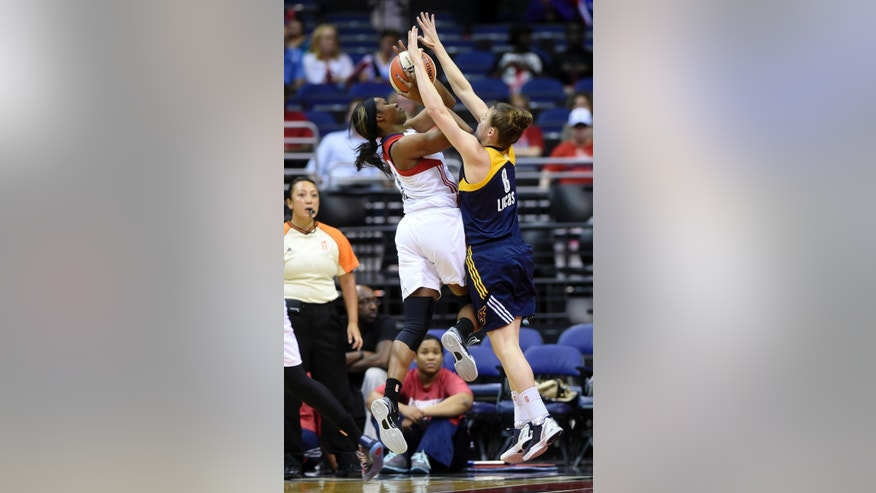 Washington Mystics guard Tayler Hill, left, looks to make a pass around Indiana Fever guard Maggie Lucas, right, during the second quarter of Game 2 of their WNBA Eastern Conference semifinal series basketball game at the Verizon Center in Washington, Saturday, Aug. 23, 2014. (AP Photo/Susan Walsh)