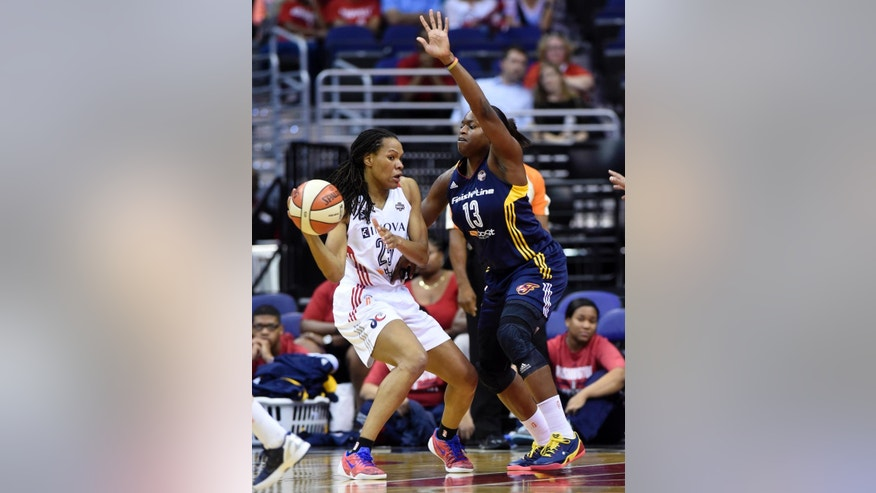 Washington Mystics forward Monique Currie, left, moves around Indiana Fever forward Karima Christmas (13) during the second quarter of Game 2 of their WNBA Eastern Conference semifinal series basketball game at the Verizon Center in Washington, Saturday, Aug. 23, 2014. (AP Photo/Susan Walsh)