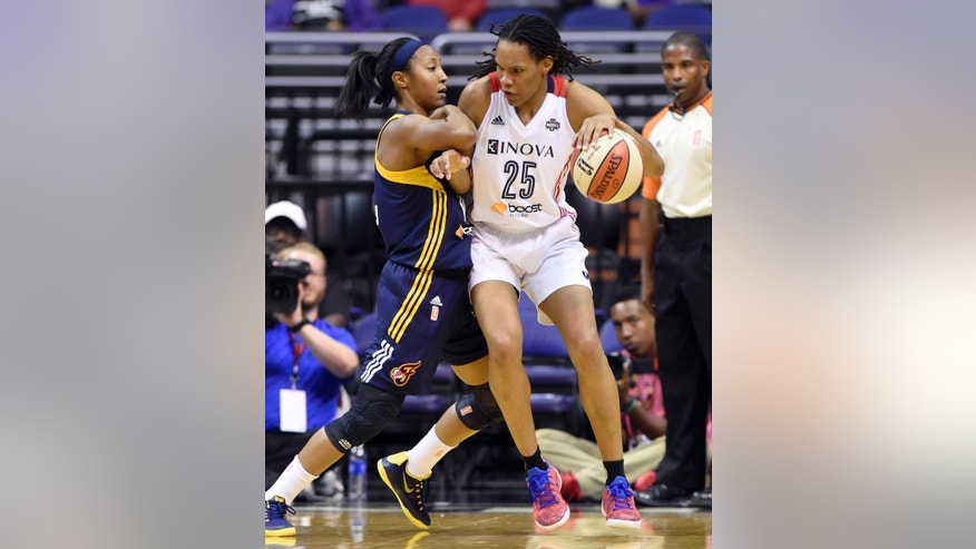 Indiana Fever guard Briann January, left, pressures Washington Mystics forward Monique Currie (25) during the second quarter of Game 2 of their WNBA Eastern Conference semifinal series basketball game at the Verizon Center in Washington, Saturday, Aug. 23, 2014. (AP Photo/Susan Walsh)
