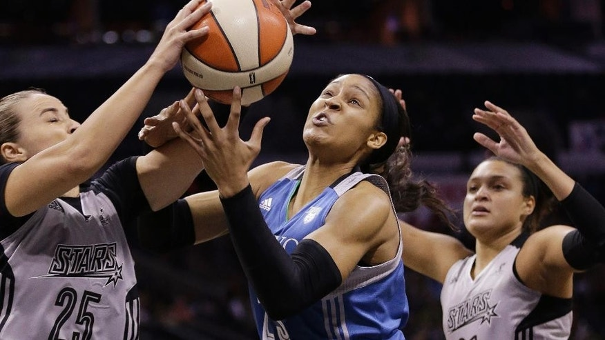 San Antonio Stars' Becky Hammon  (25) steals the ball from Minnesota Lynx's Maya Moore, center, during the first half in Game 2 of the WNBA basketball Western Conference semifinal, Saturday, Aug. 23, 2014, in San Antonio. Stars' Kayla McBride, right, assists on the play.(AP Photo/Eric Gay)