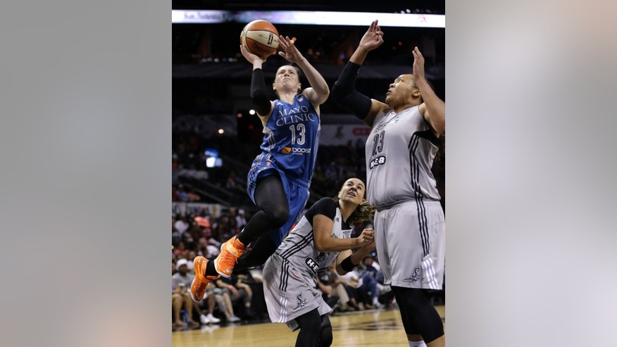 Minnesota Lynx's Lindsay Whalen (13) shoots over San Antonio Stars' Becky Hammon, center, and Danielle Adams (23) during the first half in Game 2 of the WNBA basketball Western Conference semifinal, Saturday, Aug. 23, 2014, in San Antonio. (AP Photo/Eric Gay)