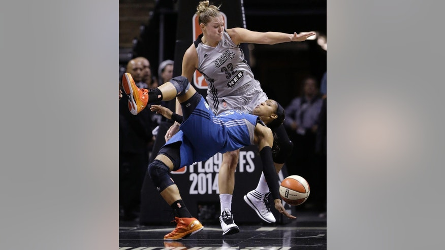 Minnesota Lynx's Maya Moore, front, falls to the court as she and San Antonio Stars' Jayne Appel battle for a rebound during the first half in Game 2 of the WNBA basketball Western Conference semifinal, Saturday, Aug. 23, 2014, in San Antonio. (AP Photo/Eric Gay)