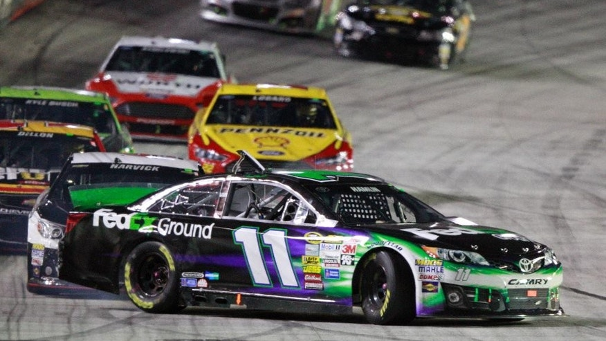 Driver Denny Hamlin (11) gets turned by driver Kevin Harvick, behind, as they come down the front straight away during a NASCAR Sprint Cup Series auto race at Bristol Motor Speedway on Saturday, Aug. 23, 2014, in Bristol, Tenn. (AP Photo/Wade Payne)