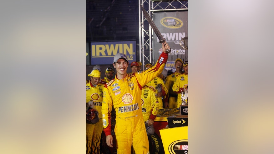 Joey Logano holds a sword presented to him after winning a NASCAR Sprint Cup Series auto race at Bristol Motor Speedway on Saturday, Aug. 23, 2014, in Bristol, Tenn. (AP Photo/Wade Payne)