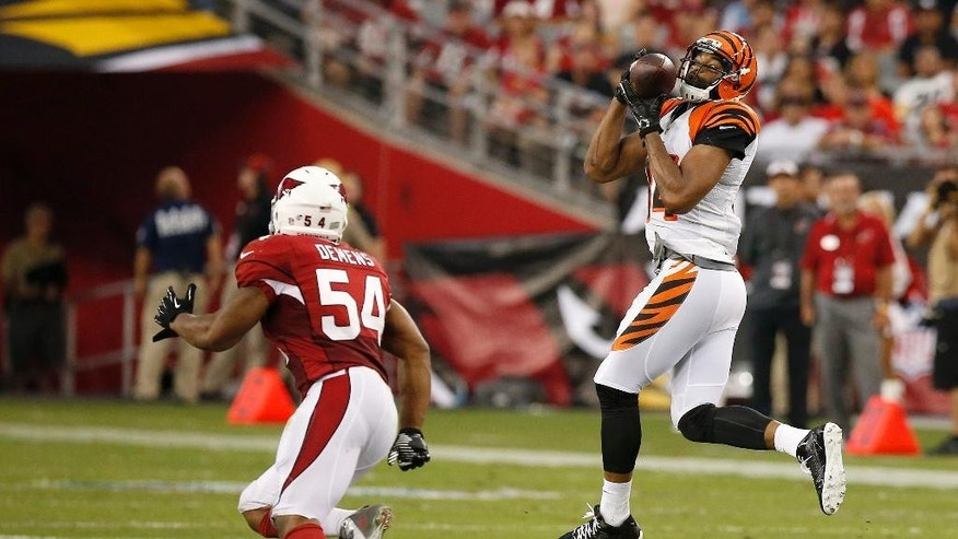 Cincinnati Bengals' Jermaine Gresham, right, makes a jumping catch in front of Arizona Cardinals' Kenny Demens (54) during the first half of an NFL preseason football game Sunday, Aug. 24, 2014, in Glendale, Ariz. (AP Photo/Ross D. Franklin)