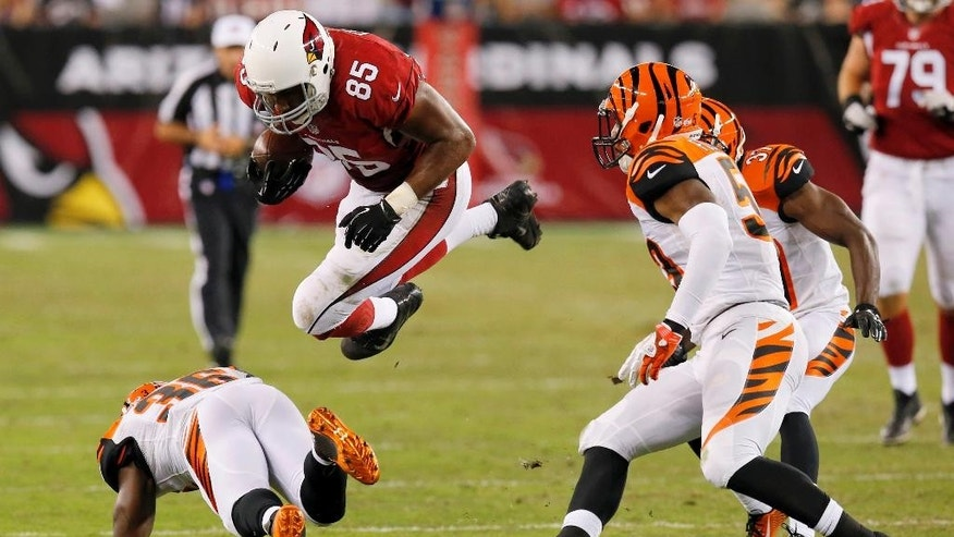Arizona Cardinals tight end Darren Fells (85) is hit by Cincinnati Bengals strong safety Shawn Williams, bottom, during the second half of an NFL preseason football game, Sunday, Aug. 24, 2014, in Glendale, Ariz. (AP Photo/Ross D. Franklin)
