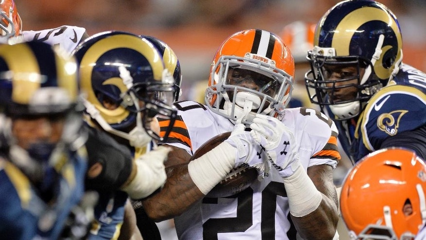 Cleveland Browns running back Terrance West (20) is stopped by the St. Louis Rams after a five yard gain in the third quarter of preseason NFL football game Saturday, Aug. 23, 2014, in Cleveland. (AP Photo/David Richard)