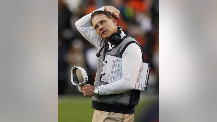 "FILE - In this Nov. 30, 2013, file photo, Auburn head coach Gus Malzahn scratches his head during the first half of an NCAA college football game against Alabama in Auburn, Ala. Malzahn often celebrates big plays with a ""Boom"" and victories with a trip to Waffle House, just like when he was coaching high school.(AP Photo/Jay Sailors, File)"