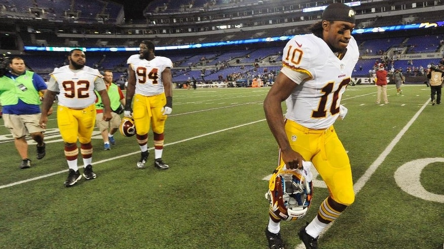 Washington Redskins quarterback Robert Griffin III, right, jogs off the field after an NFL preseason football game against the Baltimore Ravens, Saturday, Aug. 23, 2014, in Baltimore. Baltimore won 23-17. (AP Photo/Gail Burton)