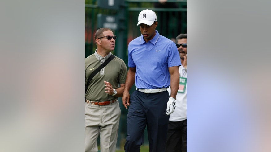 FILE - In this May 7, 2013, file photo, Tiger Woods walks with his golfing coach Sean Foley during a practice round  for the Players Championship golf tournament at TPC Sawgrass in Ponte Vedra Beach, Fla. Woods is leaving swing coach Sean Foley after four years and no majors. Woods said on his website Monday, Aug. 25, 2014, he will no longer work with Foley. (AP Photo/Gerald Herbert, File)