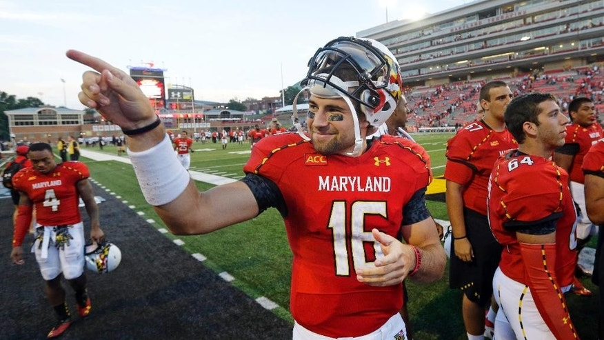 FILE - In this Sept. 7, 2013, file photo, Maryland quarterback C.J. Brown acknowledges fans in the stands after an NCAA college football game against Old Dominion in College Park, Md. Now in his sixth year at Maryland, Brown just might have attended more classes and taken more snaps than any other quarterback in the country. (AP Photo/Patrick Semansky, File)