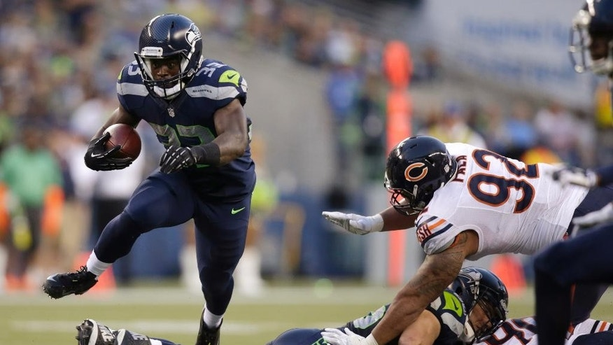 Seattle Seahawks running back Christine Michael, left, jumps over a teammate as Chicago Bears defensive tackle Stephen Paea moves in during the first half of a preseason NFL football game, Friday, Aug. 22, 2014, in Seattle. (AP Photo/Stephen Brashear)