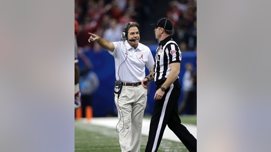 FILE - In this Jan. 2, 2014, file photo, Alabama head coach Nick Saban argues with an official in the first half of the NCAA college football Sugar Bowl against Oklahoma in New Orleans. The NCAA's switch to a 40-second play clock in 2008 altered the way college football games were managed, the pace of play no longer in the hands of the officials but the two teams' offenses. With defenses struggling to keep up, the NCAA football rules committee earlier this year looked at possibly prohibiting teams from snapping the ball until at least 10 seconds had run off the 40-second play clock. Supporters of the rule, like Arkansas' Bret Bielema and Alabama's Nick Saban, argued it was needed to allow teams to substitute for fatigued players and prevent injuries. (AP Photo/Patrick Semansky, File)