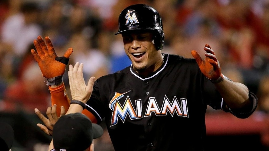 Miami Marlins' Giancarlo Stanton celebrates his home run against the Los Angeles Angels during the fourth inning of a baseball game in Anaheim, Calif., Monday, Aug. 25, 2014. (AP Photo/Chris Carlson)