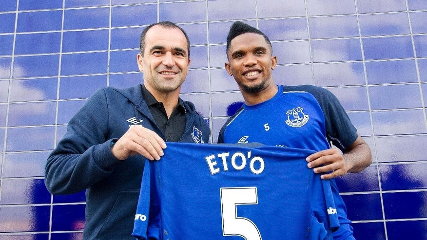 Everton's new signing Samuel Eto'o, right,  and manager Roberto Martinez pose with a shirt following a press conference in  Liverpool Wednesday Aug. 27, 2014.  Everton strengthened its attacking options by signing Samuel Eto'o on a two-year deal after the striker was released by Premier League rival Chelsea.  (AP Photo/Barry Coombs/PA)  UNITED KINGDOM OUT