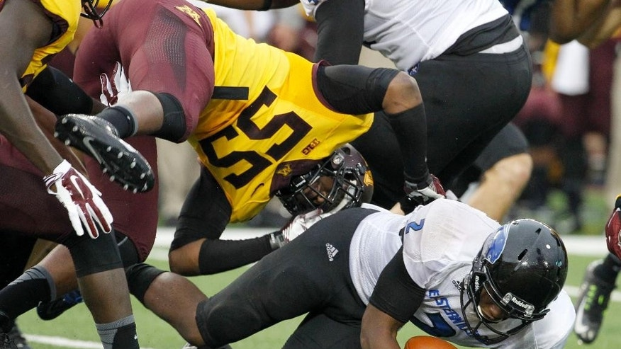 Eastern Illinois quarterback Jalen Whitlow, lands under Minnesota defensive lineman Theiren Cockran (55) after carrying the ball for a nine and 1/2-yard gain during the second quarter of an NCAA college football game in Minneapolis Thursday, Aug. 28, 2014. (AP Photo/Ann Heisenfelt)