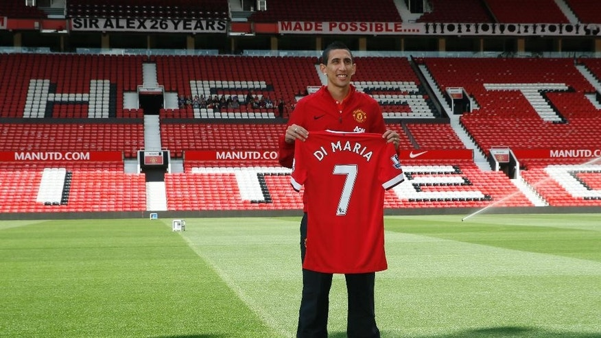 Manchester United's new player Angel Di Maria poses for photographers holding his new shirt, at Old Trafford Stadium in Manchester, England, Thursday, Aug. 28, 2014. Manchester United have signed winger Angel Di Maria from Real Madrid for a British record transfer fee of £59.7m. The Argentine winger had a medical in Manchester on Tuesday and has signed a five-year deal. (AP Photo/Alastair Grant)