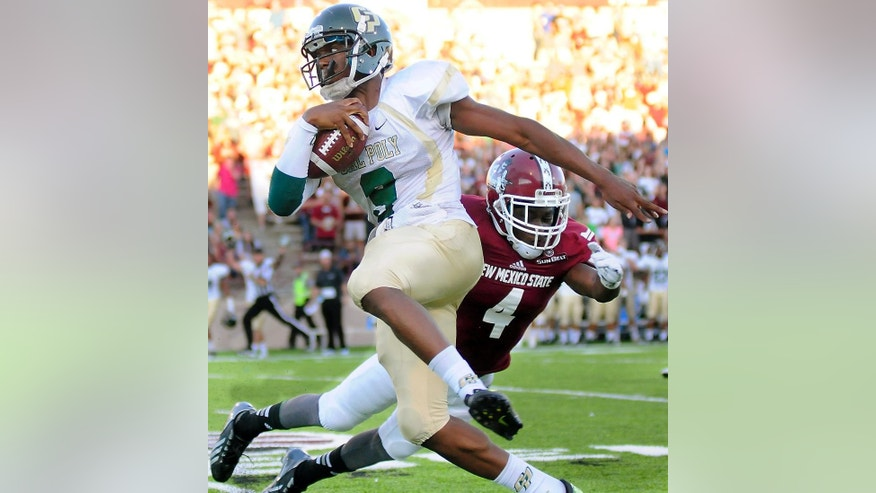Cal Poly quarterback Chris Brown dodges New Mexico State's Winston Rose during an NCAA college football game Thursday, Aug. 28, 2014, in Las Cruces N.M. (AP Photo/Las Cruces Sun-News, Robin Zielinski)