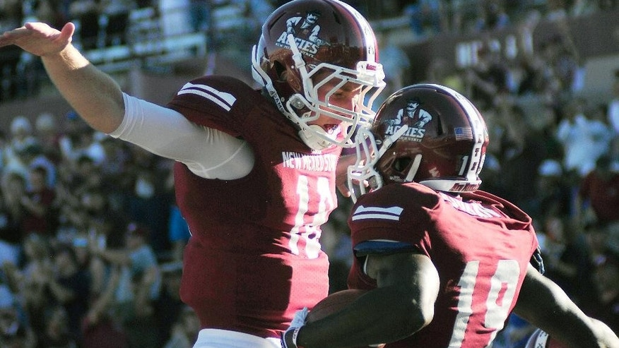 New Mexico State quarterback Tyler Rogers, left, celebrates with wide receiver Teldrick Morgan after a 30-yard touchdown pass against Cal Poly during an NCAA college football game Thursday, Aug. 28, 2014, in Las Cruces, N.M. (AP Photo/Las Cruces Sun-News, Robin Zielinski)