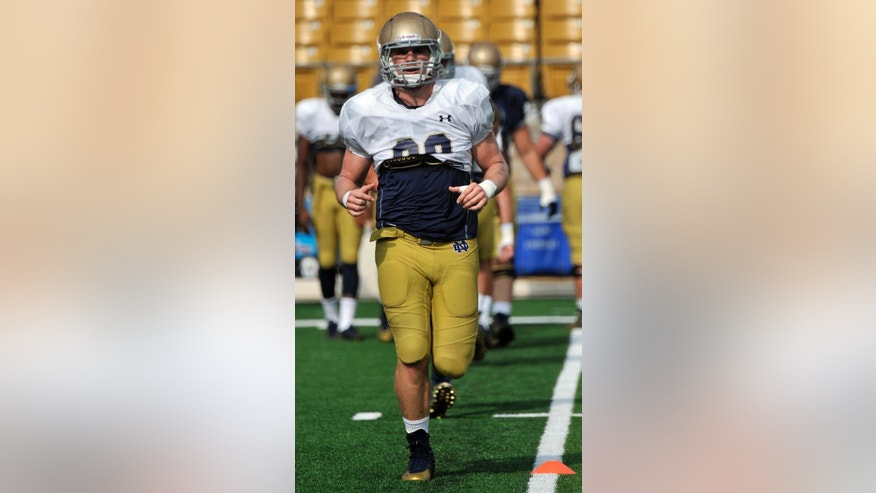 In this Aug. 19, 2014, photo, Notre Dame linebacker Joe Schmidt loosens up during media day practice of an NCAA college football team in South Bend, Ind. Schmidt doesn't believe he's made it because he's now starting middle linebacker. The 6-foot, 235-pound senior says he doesn't ever want to feel like he's made it.  (AP Photo/Joe Raymond)