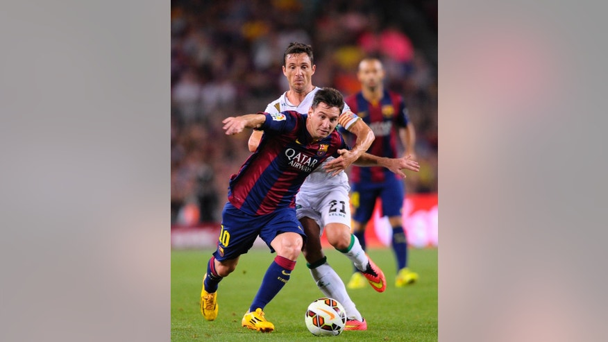 FC Barcelona's Lionel Messi from Argentina, left, duels for the ball against Elche's Edu Albacar during a Spanish La Liga soccer match at the Camp Nou stadium in Barcelona, Spain, Sunday, Aug. 24, 2014. (AP Photo/Manu Fernandez)
