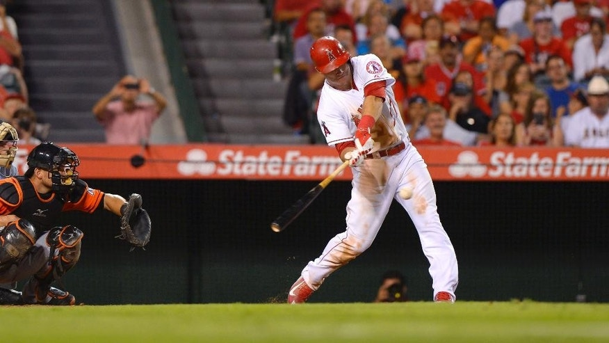 Los Angeles Angels' Mike Trout hits a solo home run in front of Miami Marlins catcher Jeff Mathis during the seventh inning of a baseball game, Wednesday, Aug. 27, 2014, in Anaheim, Calif. (AP Photo/Mark J. Terrill)