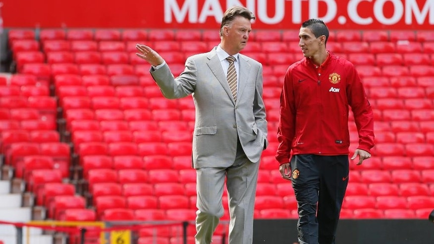 Manchester United's new player Angel Di Maria, right, and manager Louis van Gaal, pose for photographers, at Old Trafford Stadium in Manchester, England, Thursday, Aug. 28, 2014. Manchester United have signed winger Angel Di Maria from Real Madrid for a British record transfer fee of £59.7m. The Argentine winger had a medical in Manchester on Tuesday and has signed a five-year deal. (AP Photo/Alastair Grant)